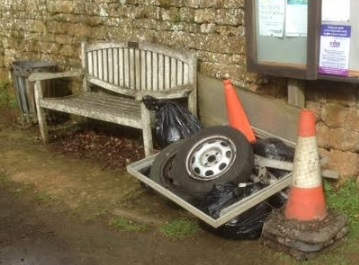 A pile of old tyres, traffics cones and bin bags, next to a wooden bench