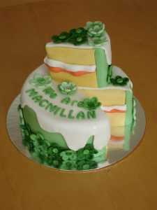 A white cake decorated with green icing the words